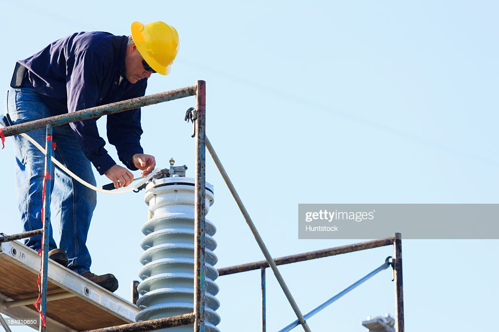 Power engineer performing maintenance on fluid filled high voltage insulator : Stock Photo