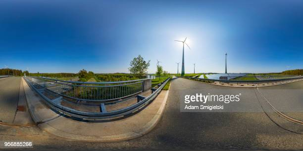 power generating wind turbines and the solar panels in the countryside (360-degree panorama) - equirectangular panorama stock pictures, royalty-free photos & images