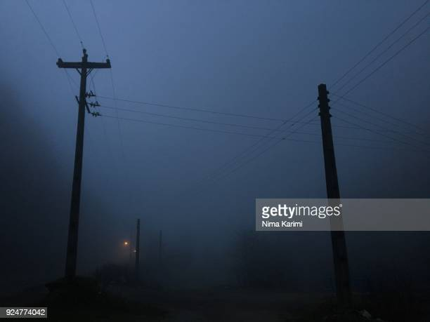 Power line poles in fog at twilight
