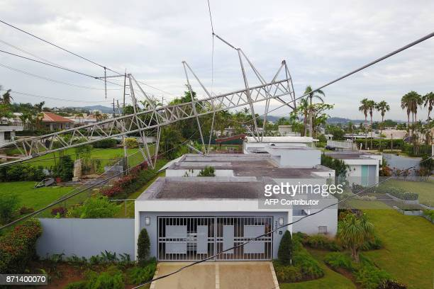 Power line tower downed by the passing of Hurricane Maria lies on top of a house in San Juan, Puerto Rico on November 7, 2017. The Center for Puerto...