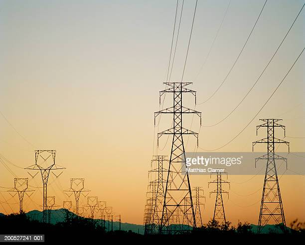 Power line towers on large field at sunset