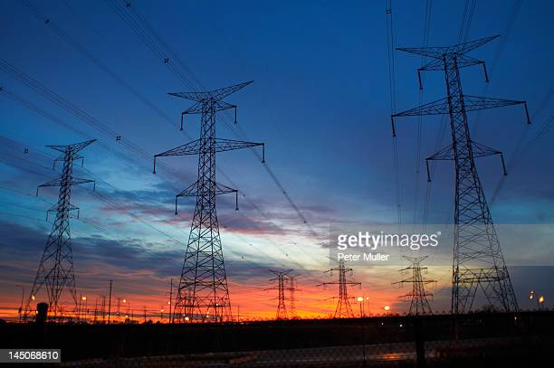 Power lines against sunset sky