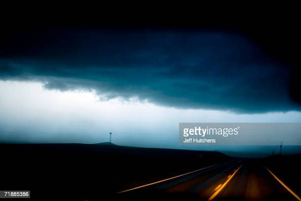 Power lines along a Nebraska country road illuminated by a Tempest Tours storm chase van's headlights are seen through a dust storm of a powerful...