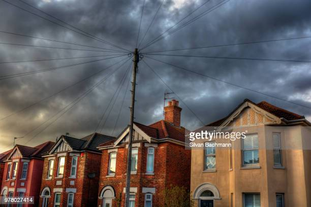 power lines connected to suburban row houses under moody sky, bournemouth, dorset, england, uk - bournemouth england stock pictures, royalty-free photos & images