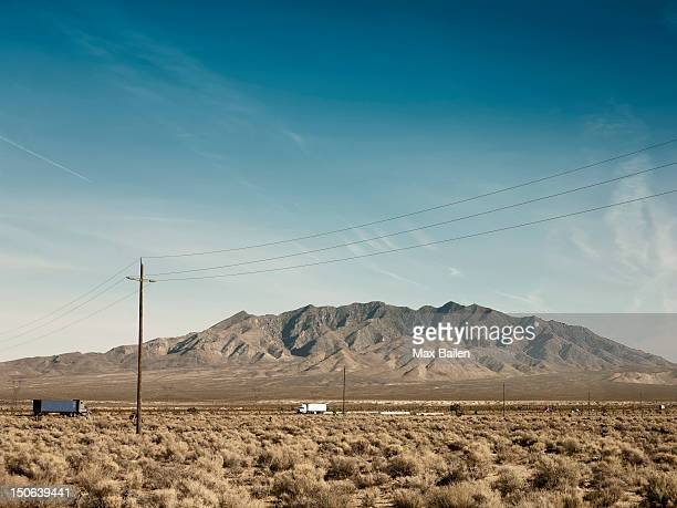 Power lines, dirt road and mountain