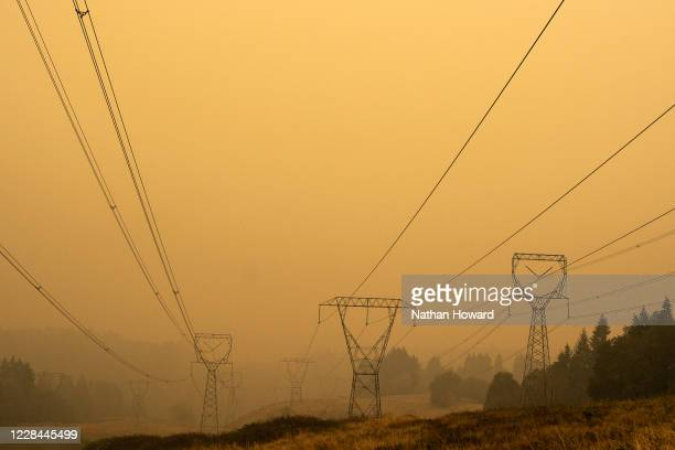 Power lines extend through heavy wildfire smoke on September 10, 2020 in Estacada, Oregon. Multiple wildfires grew by hundreds of thousands of acres...