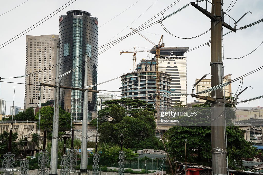 Power lines hang from pylons at a sub station as a tower stands under construction in the background in Kuala Lumpur, Malaysia, on Wednesday, May 27, 2015. Malaysia's ringgit fell for a sixth day on June 1, in the longest stretch of losses since 2013 as falling oil prices weigh on the nation's finances. Photographer: Sanjit Das/Bloomberg via Getty Images