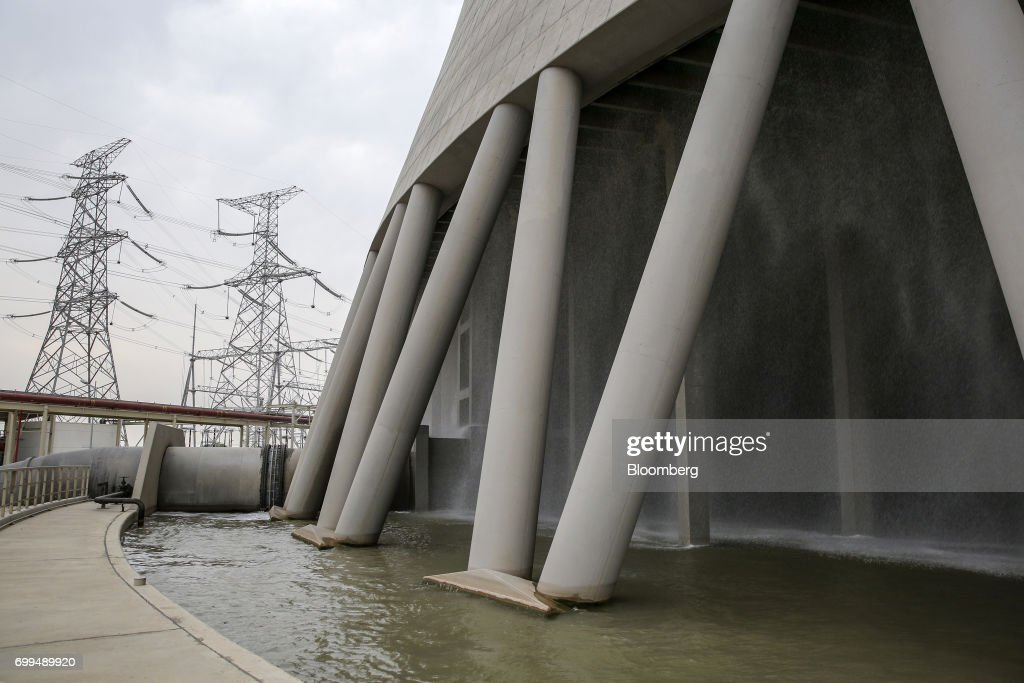 Power lines hang from transmission pylons beyond the base of a cooling tower at the Sahiwal coal power plant owned by China`s stateowned Huaneng...