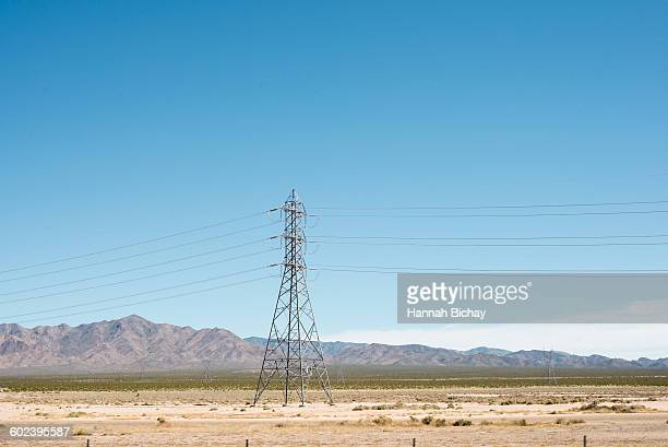 Power lines in the desert with mountains