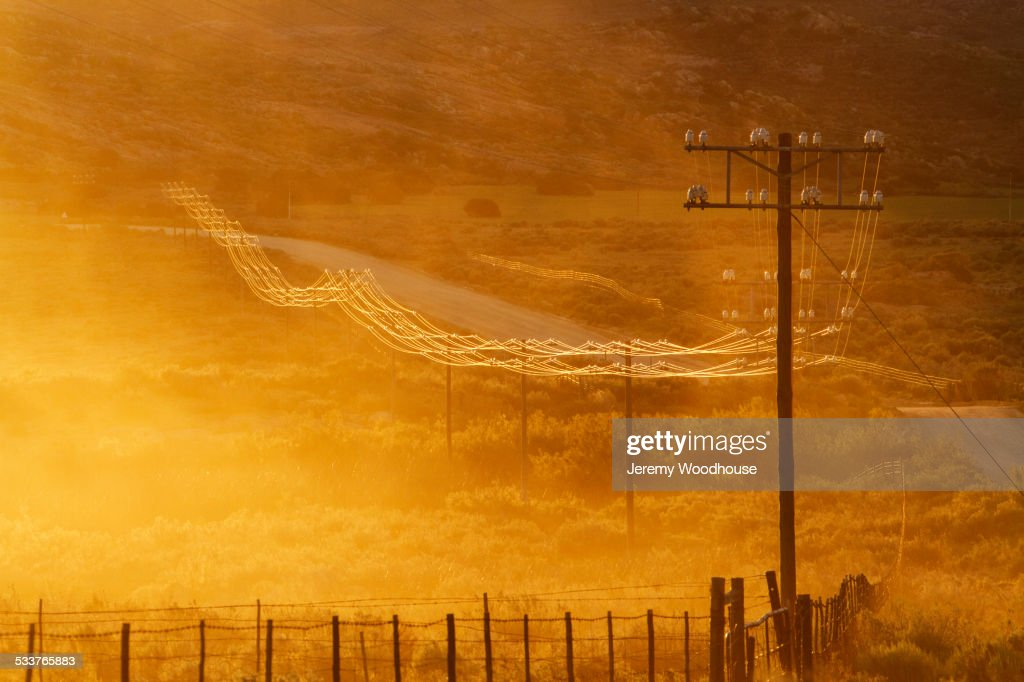 Power lines on road in grassy remote landscape : Foto stock