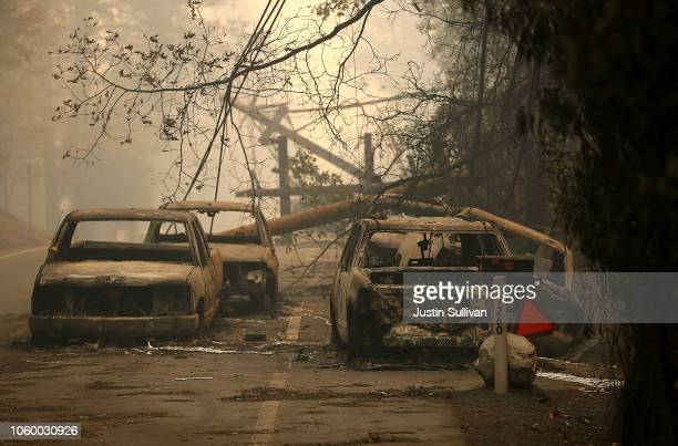 Power lines rest on cars that were burned by the Camp Fire on November 10 2018 in Paradise California Fueled by high winds and low humidity the...