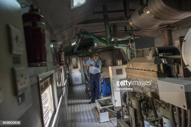 A power plant operator works in the engine room of a Green Line Express train operated by Pakistan Railways en route from Karachi to Islamabad in...