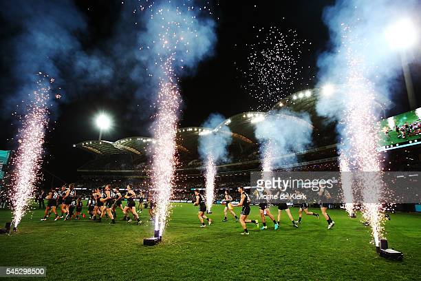 Power players run onto the field before the start of the round 16 AFL match between the Port Adelaide Power and the Hawthorn Hawks at Adelaide Oval...