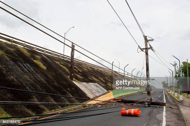 A power pole hangs from power lines on a road in the aftermath of Hurricane Irma in Luquillo Puerto Rico on September 7 2017 One of the most powerful...