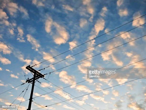 Power Pole Set Against Blue Sky & Pink Clouds