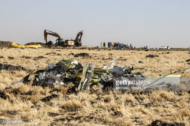 A power shovel digs next to debris at the crash site of Ethiopia Airlines near Bishoftu a town some 60 kilometres southeast of Addis Ababa Ethiopia...