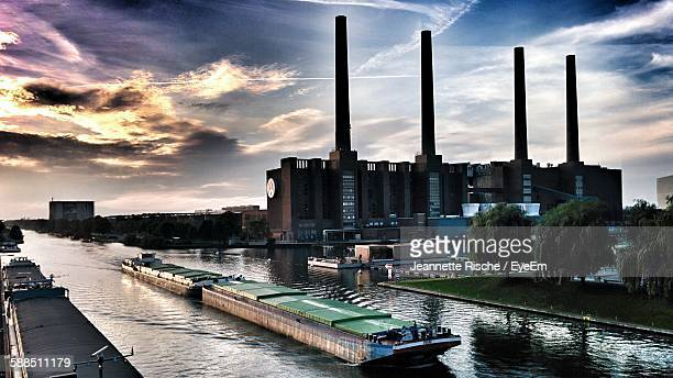 power station by canal against cloudy sky - wolfsburg lower saxony stock pictures, royalty-free photos & images