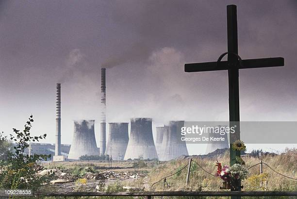 A power station in Katowice Poland with a cross and flowers in the foreground circa 1990