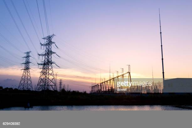 power station near water at sunrise
