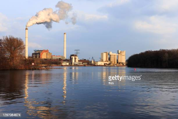power station (berlin klingenberg) with smoking stacks and nice reflection in  the water at night - district heating plant stock pictures, royalty-free photos & images