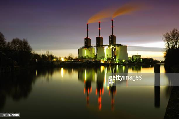 Power station (Berlin Lichterfelde) with smoking stacks and nice reflection in  the water at night