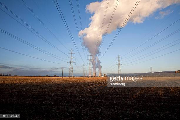Power transmission lines hang from electricity pylons as the cooling towers of Electricite de France SA's nuclear power plant emit vapor in Bugey...