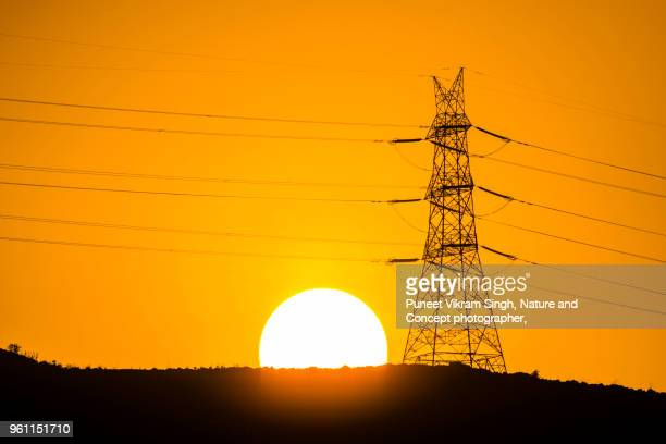 A power transmission tower and rising Sun over a hill