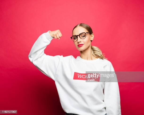 power woman in a white blouse with raised fist - authority stock pictures, royalty-free photos & images