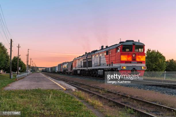 powerful diesel locomotive with a heavy freight train in a beautiful sunset light - 貨物列車 ストックフォトと画像
