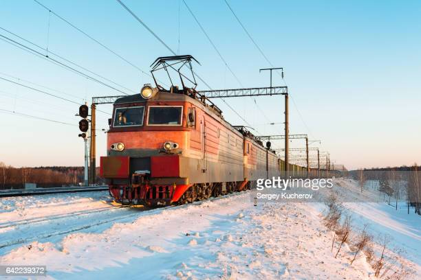 powerful electric locomotive leads freight train in sunset light - 列車の車両 ストックフォトと画像