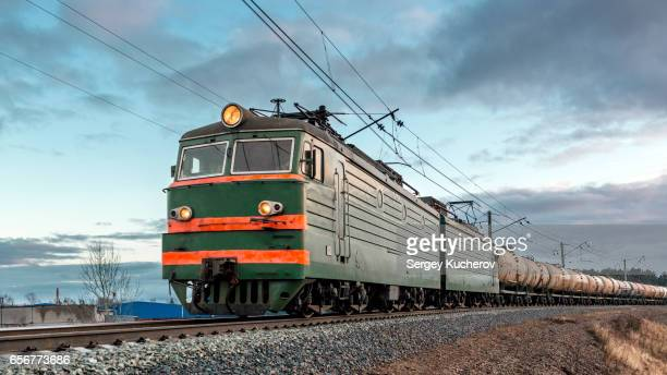 Powerful electric locomotive leads freight train with oil