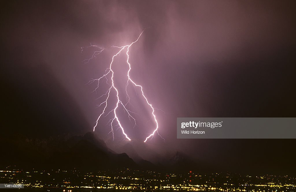 Powerful forked cloud-to-ground lightning discharge with three strike points in the Santa & Powerful forked cloud-to-ground lightning discharge with three ...