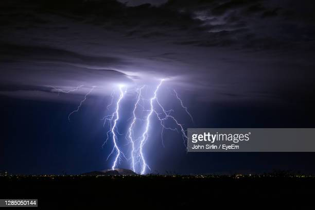 powerful lightning bolts strike a mountain during a monsoon storm near casa grande, arizona. - authority stock pictures, royalty-free photos & images
