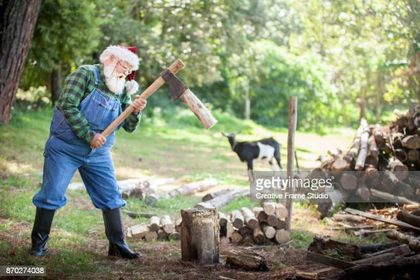 Powerful Santa Claus wood cutting on a meadow with a goat on the background.