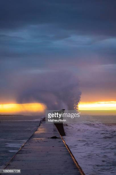 powerful storm against the coast and the harbor - levee stock pictures, royalty-free photos & images