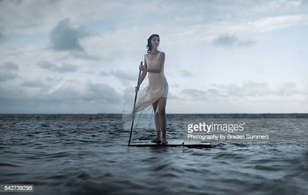 Powerful woman standing on a raft in the ocean.