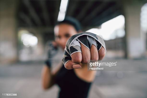 powerful young woman punching - combat sport stock pictures, royalty-free photos & images