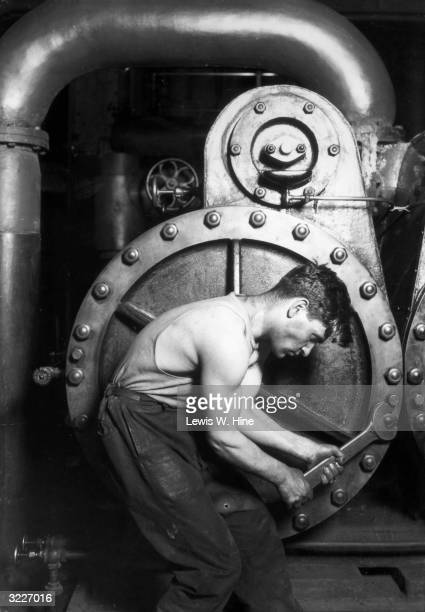 'Powerhouse Mechanic' a posed profile of a man tightening a bolt on a steam pump with a large wrench