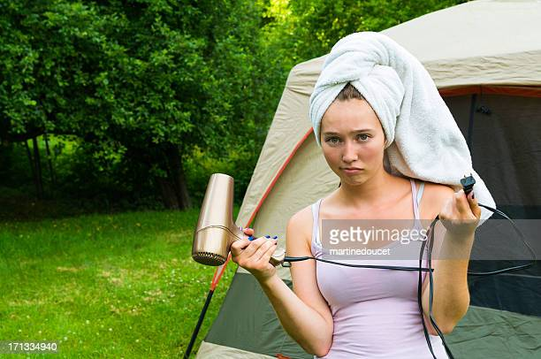 Powerless girl in camping with hairdryer, horizontal.