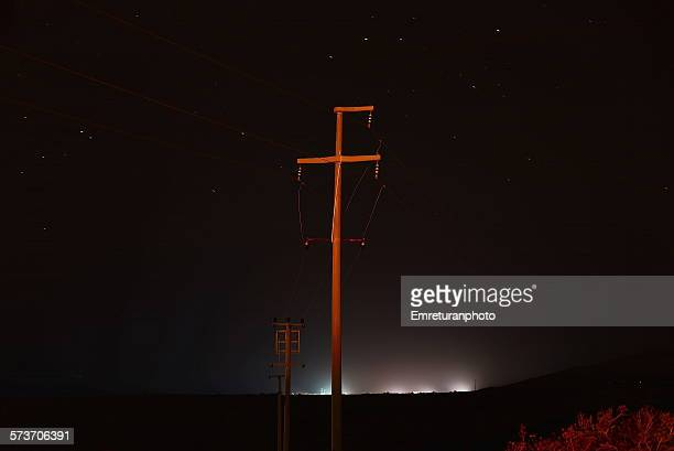 powerline under stars - emreturanphoto stock-fotos und bilder