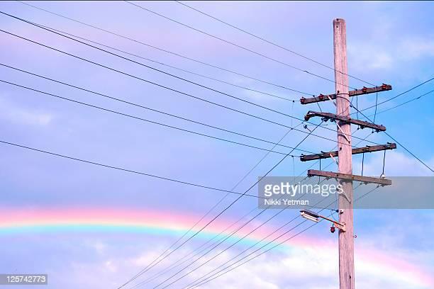 Powerlines against rainbow sky