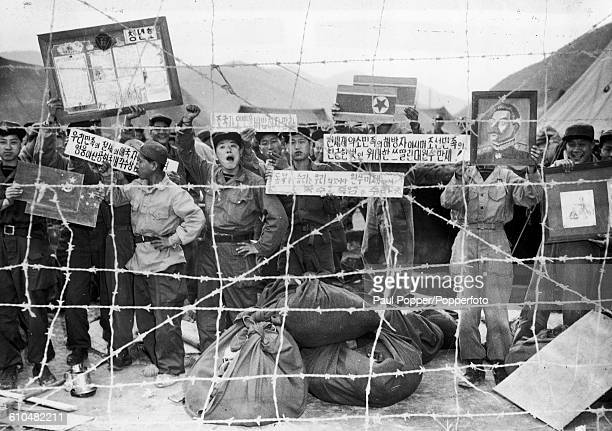 POWs in compound 76 on Koje Island during the Korean War 28th May 1952 The communist POWs hold up propaganda pictures and signs for the benefit of...