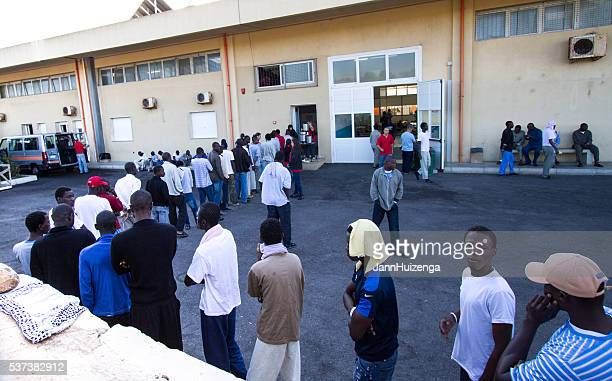 pozzallo, sicily: african migrants wait for breakfast at reception center - human trafficking stock photos and pictures