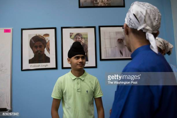 Prabhjot Singh in the library in front of a portrait of his father Prakash Singh who was killed during a mass shooting at the temple August 5 2017...