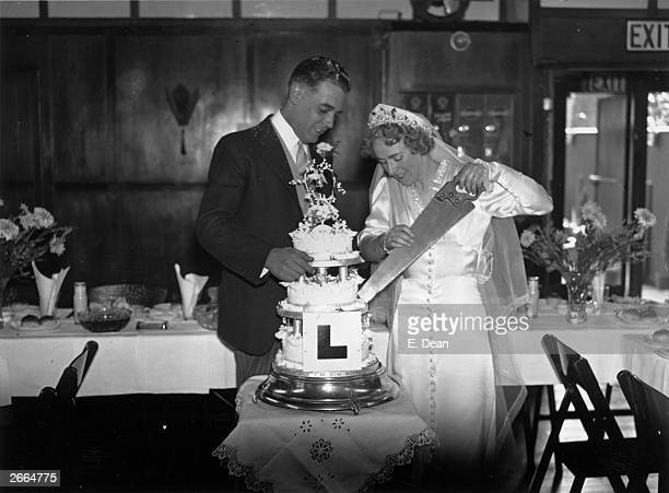 A practical joker has put a large 'L' on a wedding cake and given the bride a saw to cut it with at the wedding of Mr Donald Clements a carpenter and...