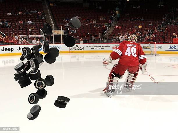 Practice pucks fly onto the ice as Mark Visentin of the Phoenix Coyotes skates to his net during pregame against the San Jose Sharks at Jobingcom...