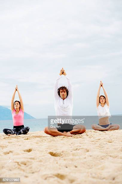 Practicing yoga and meditation in summer on beach in sunset