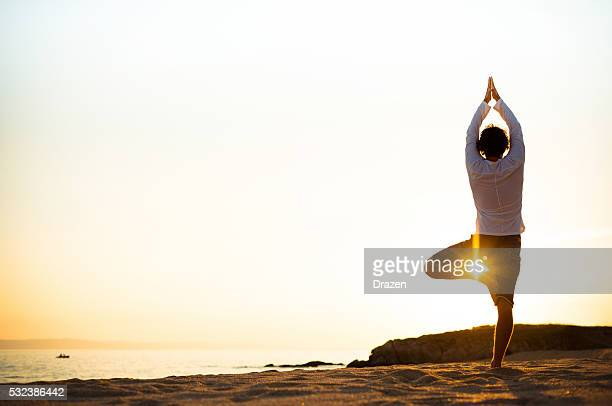 practicing yoga and meditation in summer on beach in sunset - tree position stock photos and pictures