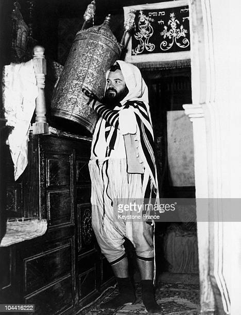 A practising Jew carrying the texts of the Torah wearing puffy pants or sarouel gri the traditional Djerbian outfit in the synagogue of La Ghriba on...