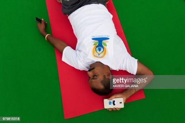 A practitioner rests on his mat as he takes part in a mass yoga session on International Yoga Day at Rajpath in New Delhi on June 21 2018...